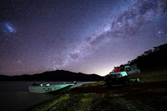Photograph of a tinny launched on lake Eildon at night with the milky way illuminating the sky